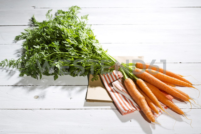 Bunch of organic carrots on cloth and white wooden table - MAEF007952