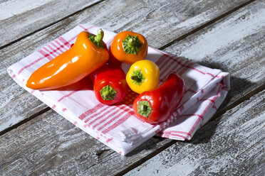 Red, orange and yellow bell peppers on kitchen towel and wooden table - MAEF007958