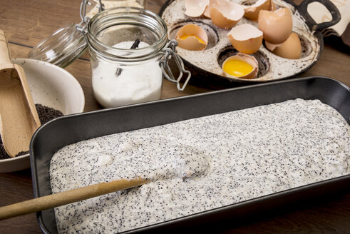 Cake pan of dough for poppy seed cake on wooden table - CSTF000065