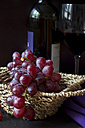 Wicker basket of red grapes (vitis vinifera), red wine glass and bottle in the background - YFF000045