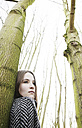 Portrait of teenage girl leaning against tree trunk - JATF000674