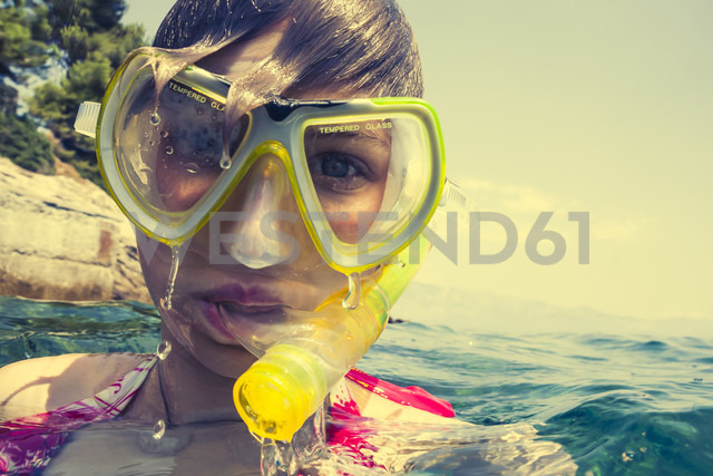Croatia, Brac, Sumartin, Teenage girl in water with diving goggles and snorkel - DISF000603