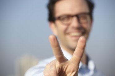 Portrait of smiling man showing victory sign - FMK000980