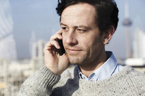 Germany, North Rhine-Westphalia , Cologne, portrait of man telephoning with smartphone - FMK000973