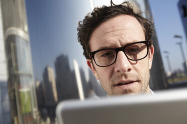 Portrait of serious looking man holding digital tablet - FMK000963