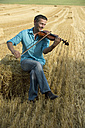 Man playing violin in stubble field - CRF002588