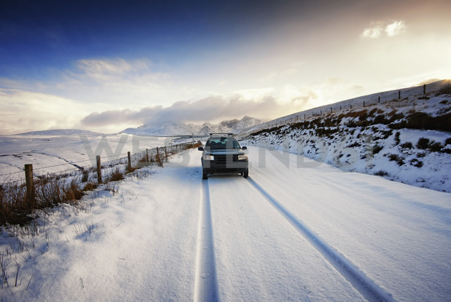UK, Scotland, Isle of Skye, Cuillin Mountains, four wheel drive vehicle driving on snow-covered street - SMAF000197 - Scott Masterton/Westend61