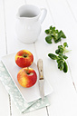 Empty jar, bowl with two apples kitchen knife and lamb's lettuce on white wooden table - EVGF000388