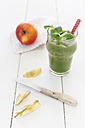 Glass of apple lamb's lettuce smoothie with spoon, apple, kichen knife on white wooden table - EVGF000394