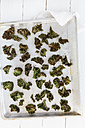 Baking tray of curly kale chips, elevated view - EVGF000408