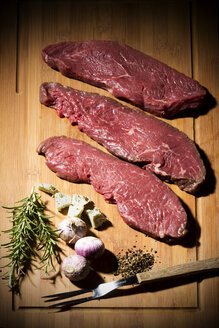 Beefsteak, garlic, rosemary, herb butter and pepper on chopping board - MAEF007988