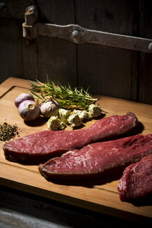 Beefsteak, garlic, rosemary, herb butter and pepper on chopping board - MAEF007986