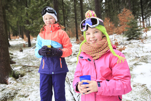 Two teenage girls wearing colourful winter clothes having a break - VTF000115