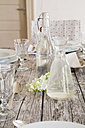 Water bottle, carafe, glasses and white blossom on festive laid table - LVF000747