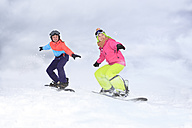 Two happy teenage girls snowboarding - VTF000120