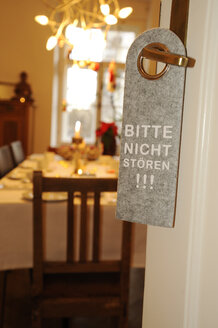 Sign 'do not disturb' at door of hotel room in front of laid table - LB000591