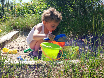 Denmark, Henne beach, summer day with a child in a sandbox - AFF000001