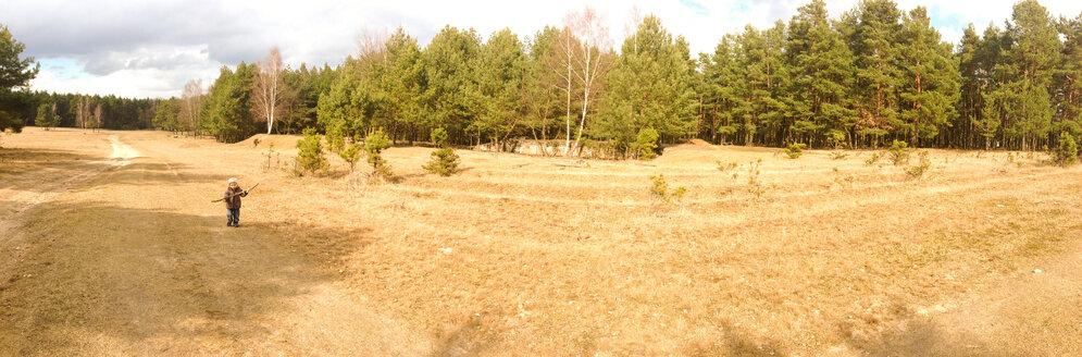 Germany, Brandenburg, Saarmund, child running on a field, forest in the background - AFF000025