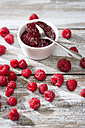Bowl of raspberry jam, spoon and raspberries on wooden table - MAEF008002