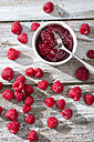 Bowl of raspberry jam, spoon and raspberries on wooden table, elevated view - MAEF008000