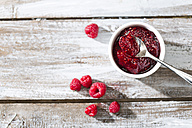 Bowl of raspberry jam, spoon and raspberries on wooden table, elevated view - MAEF007997