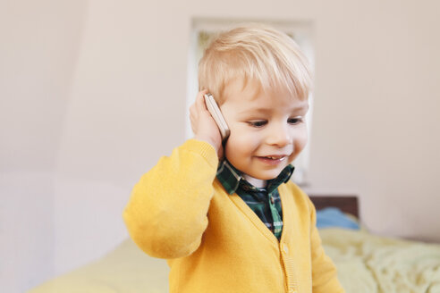 Portrait of smiling toddler telephoning with smartphone - MFF000911