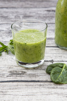 Glass bottle and glass of green smoothie made of spinach, rocket salad, apple, orange, banana and cucumber, on grey wooden table - LVF000761