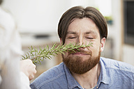 Man smelling at twig of rosemary - FMKF000992