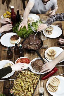 Friends eating potatoes, steaks and meatballs at wooden table - FMKF001073