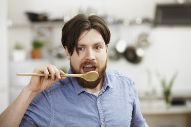 Man cooking in kitchen tasting from wooden spoon - FMKF001044