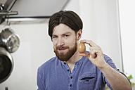 Man in kitchen holding egg - FMKF001047