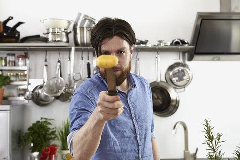 Man skewering potatoes in kitchen - FMKF001060