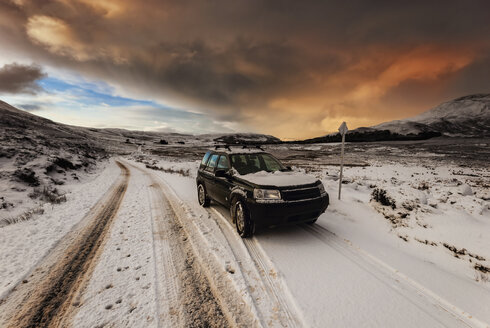 United Kingdom, Scotland, Isle of Skye, off-road vehicle at sundown in winter - SMA000199