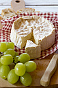 Green grapes, camembert and baguette on chopping board - SARF000295
