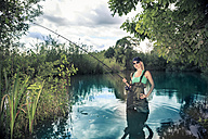 Blond woman fishing in a lake - VTF000126