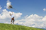 Austria, Salzburg State, Altenmarkt-Zauchensee, teenager throwing Palmbusch up in the air - HHF004771