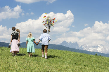 Austria, Salzburg State, Altenmarkt-Zauchensee, four children with Palmbusch walking on alpine meadow - HHF004773