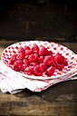 Dish of raspberries on kitchen towel and wooden table - MAEF008066
