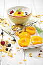 Bowl of lactose-free yogurt with pieces of peach, raspberries, blueberries and cereals on white wooden table - MAEF008088