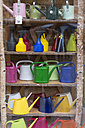 Shelf with coloured watering cans and spray bottles - HL000417