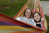 Portrait of mother and daughter lying in hammock - LB000613