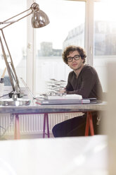 Portrait of young architect sitting at desktop in his office - FKF000420