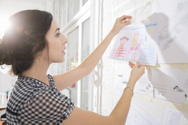 Portrait of young female architect fastening child's drawing on pin board - FKF000436