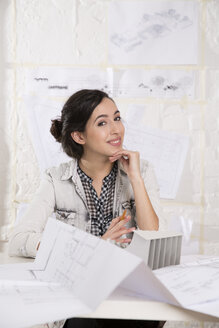 Portrait of young female architect sitting at her desktop in office - FKF000448
