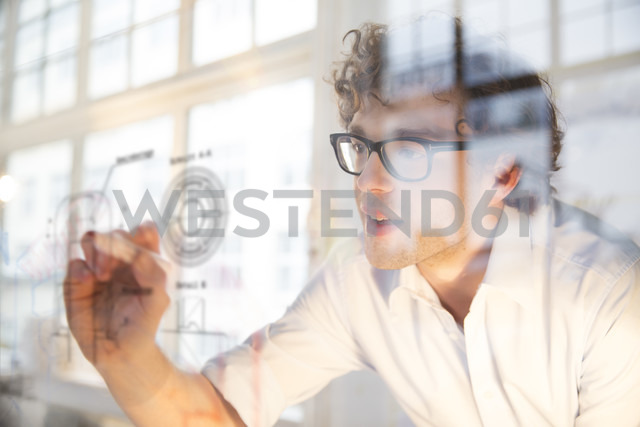 Portrait of young architect marking construction plan in office - FKF000455