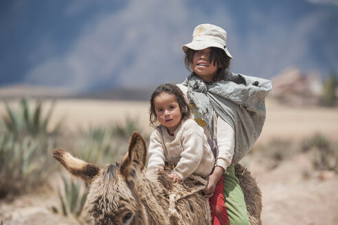 Peru, Maras, Indio woman riding on donkey with daughter - PA000512