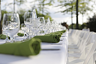 Festive laid table with green napkins and wine glasses, partial view - JATF000695