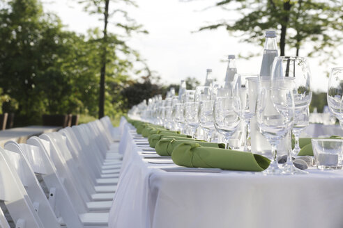Festive laid table with green napkins and wine glasses - JATF000691