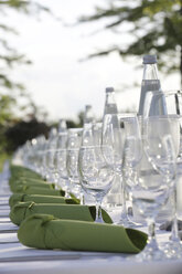 Festive laid table with green napkins, water bottles and wine glasses - JATF000690
