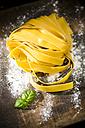 Fresh Pappardelle classico, basil and flour on wooden table - MAEF008105
